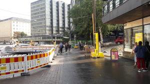 En gata med några några byggarbeten och en Uff-butik. Det är dag och trottoaren är våt.