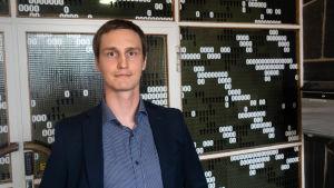 Tommi Lahtinen står i kavaj och skjorta framför en vägg som där dekorerad med ettor och nollor.