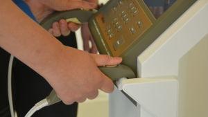 Närbild på händer som håller i handtag som hör till en apparat som mäter fettprocent, muskelmassa, proteiner med mera.