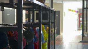 Ytterläder händer på knaggar i en skolkorridor.