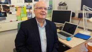 Professor Peter Lund på Aalto-universitetet sitter i ett kontor och tittar in i kameran.