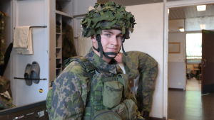 Undersergeant Tuomas Toukosalo i militärstugan iklädd stridsmundering med kamoflagehjälm