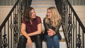 Eva Frantz och Hannah Norrena sitter i en trappa och skrattar.