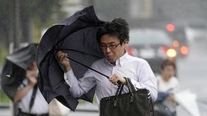 Fotgängare kämpade sig fram i vinden och regnet i Tokyo på måndag morgon.