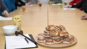 Kokouksen osallistujia pöydän äärellä. Pöydällä puheenjohtajan nuija, tilinpäätös ja pullaa tarjottimella. Kahvikuppeja.