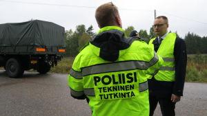 En polis och en advokat i gula kläder diskuterar i närheten av en plankorsning.