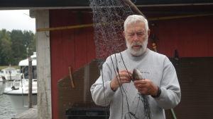 En man i grått hår rensar ett nät med en abborre i.