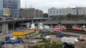 Brandbilar på en byggarbetsplats. I bilden kan man se flera brandbilar, i alla fall fem stycken.