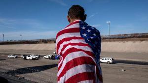 En centralamerikansk migrant insvept i USA:s flagga ser ut över Tijuana-flodens så gott som torra flodbädd på den mexikanska sidan om en gränsövergång mot USA. Bilden är tagen 25.11.2018.