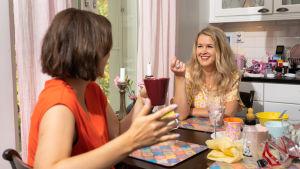 Eva Frantz och Hannah Norrena sitter vid ett köksbord och pratar.
