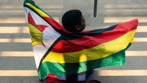 ett barn håller Zimbabwes flagga medan han sitter på den nationella sportstadion där Mugabes begravningsceremoni ska hållas i Harare