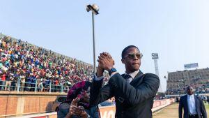 Robert Mugabe junior hälsar på folket som har samlats för att se den framlidne presidenten Robert Mugabe som liggaer på lit de parade.