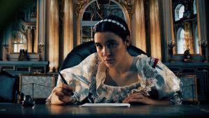 Nainen vanhassa salissa kirjoittamassa jotain paperille.