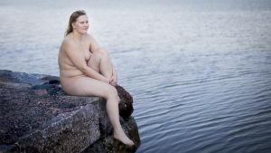 Emilia Lagergren utan kläder på en klippa.