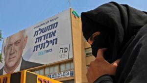En beduinkvinna passerar en av Gantz' valaffischer i Beersheva, i södra Israel.