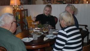 Ellen Järvinen äter vid ett bord med gäster i Café Källarvinden