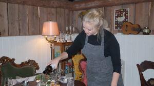 Ellen Järvinen häller upp vin i glas på dukade bord