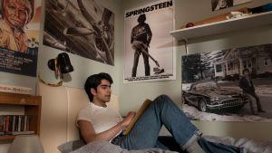 Javed (Viveik Kalra) sitter på sin säng och lyssnar på Bruce Springsteen.