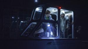 Täyteen ahdettu moottorivene pimeällä merellä. Matkustamon ovella seisoo Heikki Kinnusen näyttelemä Marta-Terttu Zeppelin hylkeennahkahaalarissa.