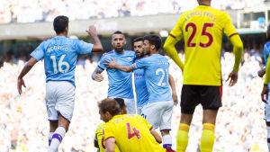 Manchester City firar mål bakom Watfordspelare.