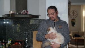 Thomas Lagerroos står i sitt kök med en lurvig katt i famnen
