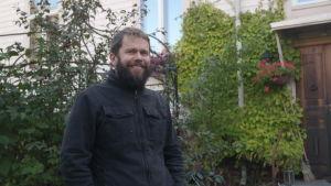 John Björkman står framför ett trähus på en lummig gård i Åbo