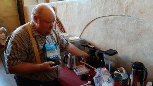 Magnus Taxell, en man med rödaktig mustasch och skägg, rutig skjorta och gyllene hängslen, kokar kaffe inför kyrkkaffet i Åbo Domkyrkas sakristia.