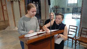 Mirjam Lillhannus, en flicka med hästsvans och grå tröja, står vid en pulpet i Åbo Domkyrka. Pastor Sofia Liljeström visar vilket stycke som ska läsas ur Bibeln i samband med en högmässa.