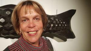 Bild på Ilona Rista som ler mot kameran med konstverk i bakgrunden.