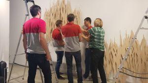 Fyra män och en kvinna monterar upp utställningen av Ilona Ristas träelement.