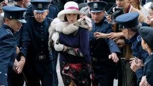 Maria Åkerblom (Pihla Viitala) går genom en folkhop som poliser tränger undan.