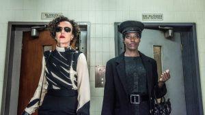 Kaksi naista tuimilla ilmeillä alaviistosta kuvattuna, takana kaakeliseinä ja vessan ovet.