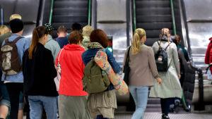 Ihmisiä astumassa ulos metrojunasta, metro Rautatieasema, liukuportaat