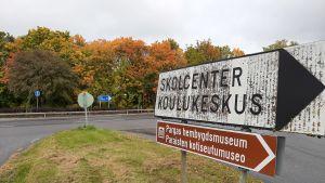 En vit vägskylt med texten Skolcenter Koulukeskus, och en brun skylt med texten Pargas hembygdsmuseum, i en vägkorsning med höstruska i träden i bakgrunden.