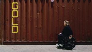Anna Giss istuu pyörätuolissa työmaaparakin edessä. Parakin seinään on kiroitettu keltaisilla isoilla kirjaimilla sana gold. Annan katse on suuntautunut tekstiin, hän on profiilissa kameraan päin.