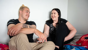 Muuttopäiväkirjat-ohjelman Väinö ja Anni istuvat sängyllä katsoen toisiinsa nauravaisina.