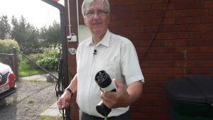Thomas Lindroos i Sibbo visar upp sin elbilsladdare