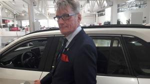 Vd Mikko Huopalainen poserar framför en bil i en bilaffär.