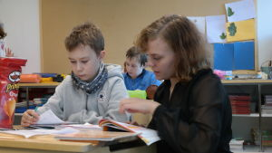 elev och lärare vid en pulpet och tittar i en bok