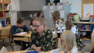 Skolassistent Eva Salminen bland elever i ett klassrum