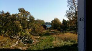 En sommarstuga med stor tomt i skärgården då gräset och träden redan börjar bli höstgula.