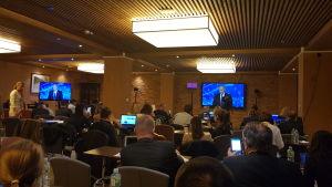 Ett pressrum med en stor teve som med Vladimir Putin.