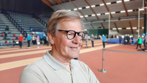 En äldre man står inne i en idrottshall