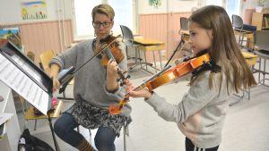Opettaja opettaa tyttöä viulunsoitossa