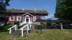 En röd stor stuga med vita knutar. På gräsmattan framför finns kafébord och kaféstolar.