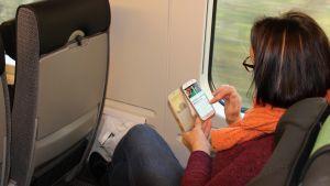 Nainen selaa nettiä kännykällään junassa.