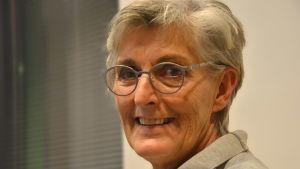 Margita Vainio, en glad dam med grått hår och glasögon med silverfärgade skalmar.