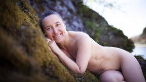 Petra Blomqvist naken på ett berg med mossa.
