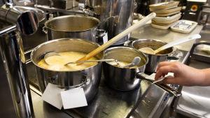Skolmat tillreds samtidigt i flera stora kastruller på en spis.