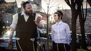 Ortodoksijuutalainen mies ja poika keskustelevat kadulla.